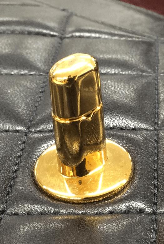 本物(1995年製造のラムスキン)のターンロックの真ん中に取り付けられた金具